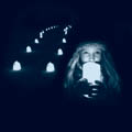 young girl holding candle in front of luminaries
