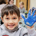 young boy with hand covered in blue paint