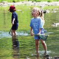 Two children playing in Holes Creek, Hidden Meadows Day Camp