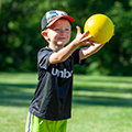 young boy caching a yellow ball