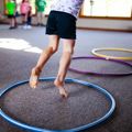 child's feet jumping in hula hoops