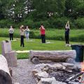 five women practicing yoga near campfire