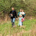 family walking in meadow in spring