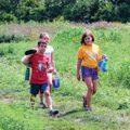 3 children walking in meadow at Bill Yeck Park