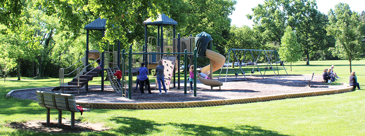 Families playing on Pleasant Hill Park playground equipment
