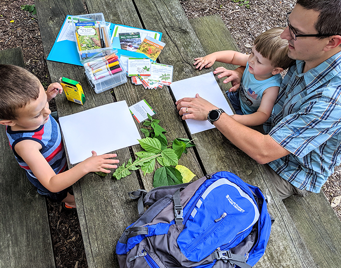 father and two children leaf rubbing at picnic table with adventure backpack