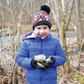 boy in winter coat and hat holding rock