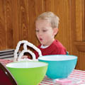 child with mixing bowls and science experiment