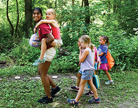 CWPD youth volunteer with four children at camp