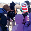 kids and program leader examining an object found on their hike