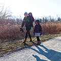 mom and daughters walking along trail in winter coats