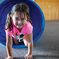 young girl crawling out of a play tunnel