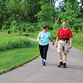 man and woman walking paved path at Oak Creek South Park