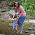 mom and baby daughter holding hands in creek
