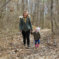 woman and young girl walking on wooded trail