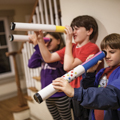three children looking through homemade telescopes