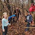 three kids and young adult making a tree fort with long branches