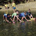 four children sending boats down Holes Creek in Grant Park