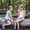 two girls sitting on log at fire circle