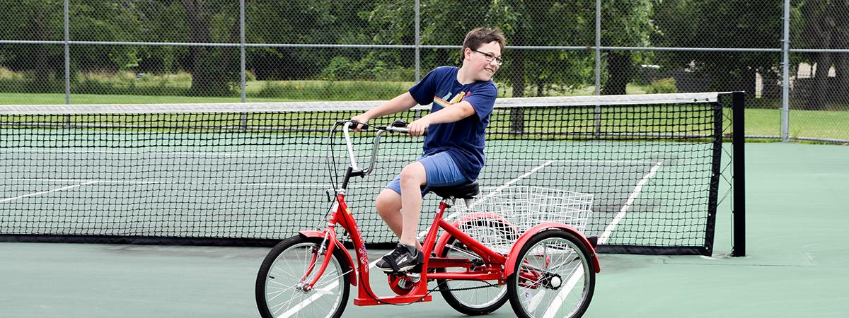 boy riding adapted bike on tennis court at Oak Grove Park