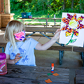 girl in mask sitting at picnic table holding up flower artwork