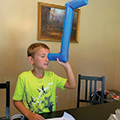boy looking through homemade pool noodle periscope