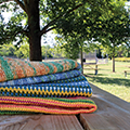 pile of knit and crocheted blankets on a picnic table