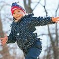 young girl running outside in her winter coat and hat