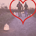 heart overlaid on photo of couple holding hands on trail with luminaries