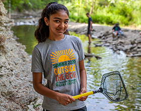 teenage girl standing in Holes Creek with a net. Wearing a CWPD summer camp t-shirt.