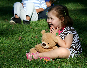 young child sitting in grass holding teddy bear