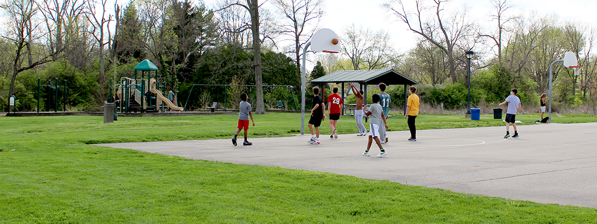 boys playing basketball at Concept Park, playground and shelter in background.