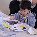 little boy painting a canvas