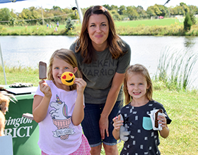 woman and two young girls standing in front of Oak Grove Park pond holding sweet treats