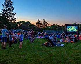 crowd surrounding outdoor movie screen at sunset, Forest Field Park