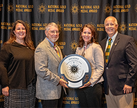 four people holding a gold medal plaque in front of a photo backdrop